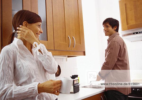 Frau lächelt den Mann an  der Geschirr spült.