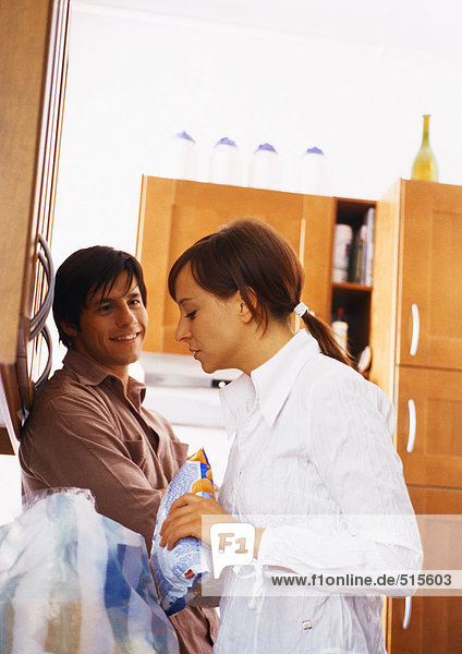 Man smiling at woman in kitchen.