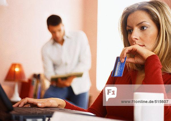 Frau mit Computer und Kreditkarte  Mann liest im Hintergrund.