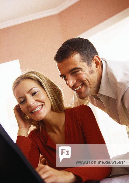 Mann schaut über die Schulter der Frau mit dem Computer.