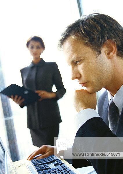 Geschäftsfrau im Hintergrund stehend  verschwommen  Geschäftsmann am Computer sitzend  Seitenansicht  Nahaufnahme