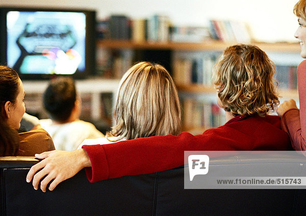 People sitting on couch watching TV  rear view