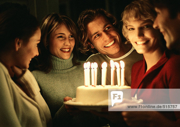 Woman holding birthday cake in group