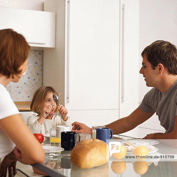 Mutter und Vater mit Tochter am Frühstückstisch
