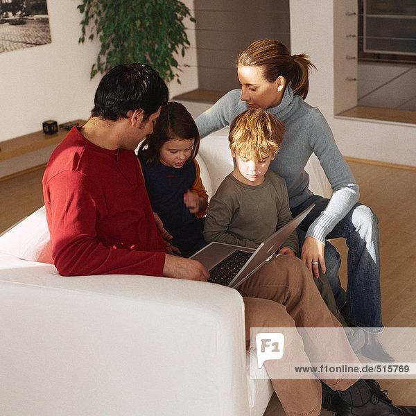 Familie sitzt zusammen auf dem Sofa und schaut auf den Laptop.