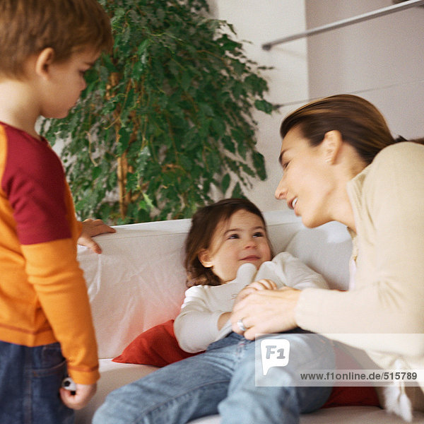 Woman holding daughter on couch  son standing nearby