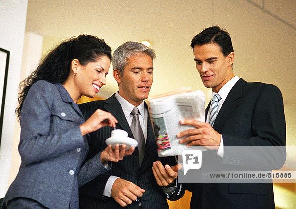 Gruppe von Geschäftsleuten  die gemeinsam Zeitung betrachten  Taille nach oben  Blickwinkel niedrig