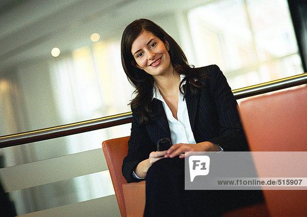 Geschäftsfrau sitzend  lächelnd vor der Kamera  Portrait  Neigung