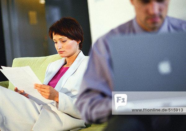 Geschäftsfrau beim Betrachten von Dokumenten in der Nähe von Geschäftsleuten auf dem Computer  unscharf