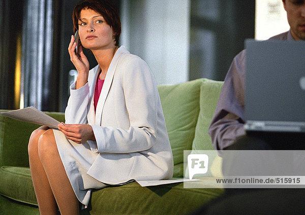 Geschäftsfrau sitzend mit Handy  Mann mit Laptop