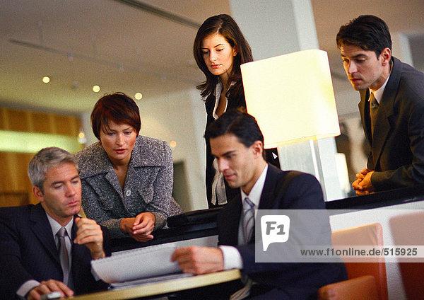 Gruppe von Geschäftsleuten  stehend und sitzend  Dokument betrachtend  neigend
