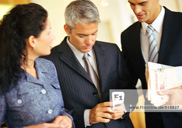 Geschäftsmänner und Geschäftsfrau  eine hält ein Handy.
