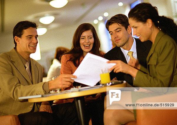 Gruppe von Menschen  die zusammensitzen und sich das Dokument ansehen