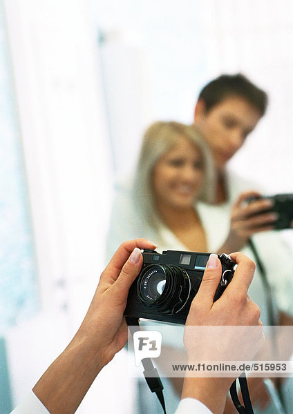 Man and woman taking photo of themselves in front of mirror  cropped view