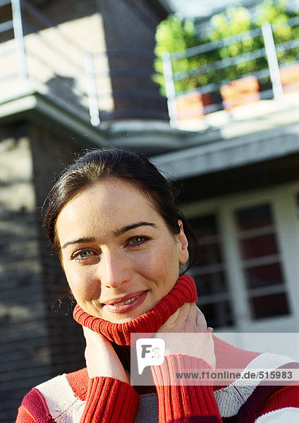 Young woman in front of house with hands on neck  smiling at camera