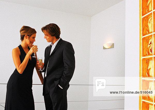 Gut gekleidetes Paar  das Champagner trinkt und redet