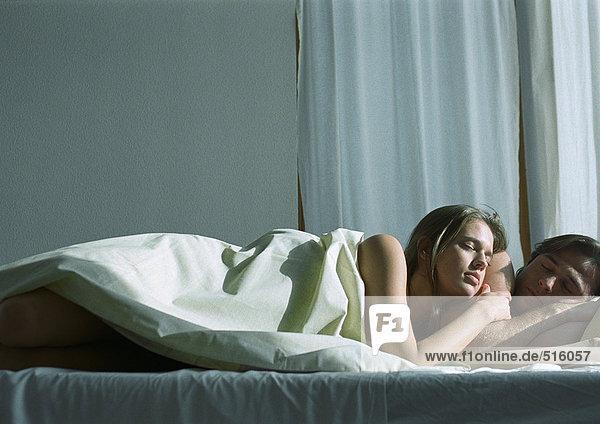 Paar schläft zusammen im Bett