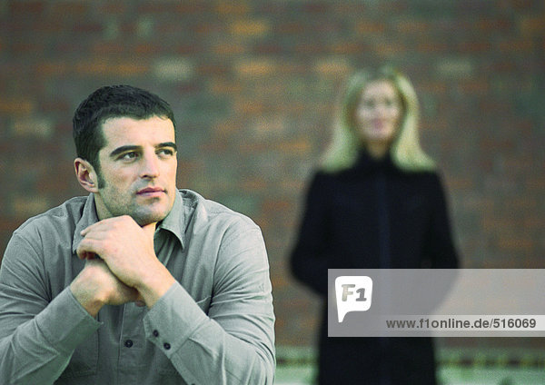 Man looking away in thought  woman blurred in background