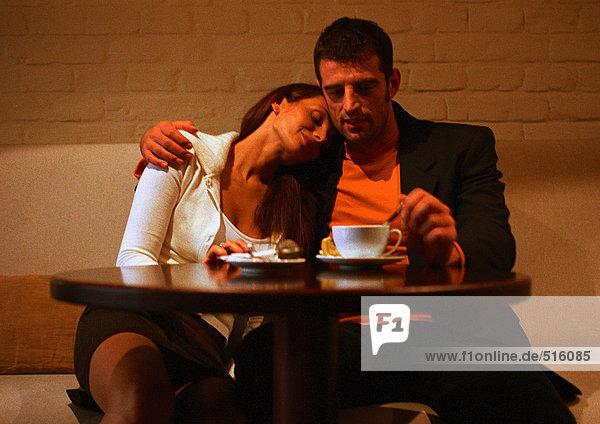 Mann und Frau sitzen am Tisch  Frau stützt sich auf die Schulter des Mannes.
