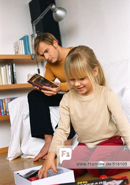 Tochter sieht sich Objekte in der Kiste an  Vater liest in der Nähe.