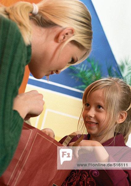 Frau hält Einkaufstasche  kleines Mädchen schaut zur Frau  hält andere Seite der Einkaufstasche  Nahaufnahme