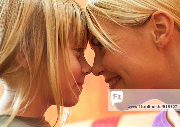Young woman and little girl smiling with foreheads and noses touching  side view  close-up  head shot
