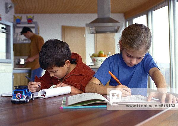 Sohn und Tochter schreiben am Tisch  Vater im Hintergrund kochend  verschwommen.