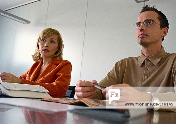 Geschäftsmann und Geschäftsfrau sitzen nebeneinander am Tisch.