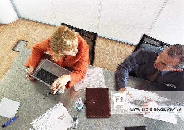 Geschäftsmann und Geschäftsfrau sitzen am Tisch und reden  Blick von oben  verschwommen.