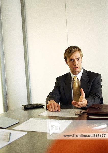 Ein Geschäftsmann sitzt am Tisch und redet.