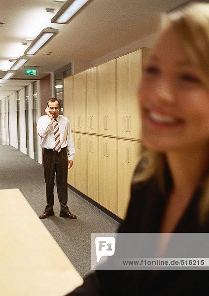Geschäftsfrau lächelnd  Mann am Telefon im Hintergrund  verschwommen.