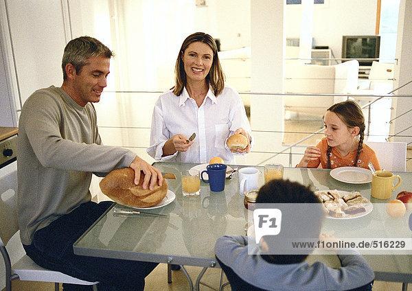 Eine vierköpfige Familie  die sich hinsetzt und isst.