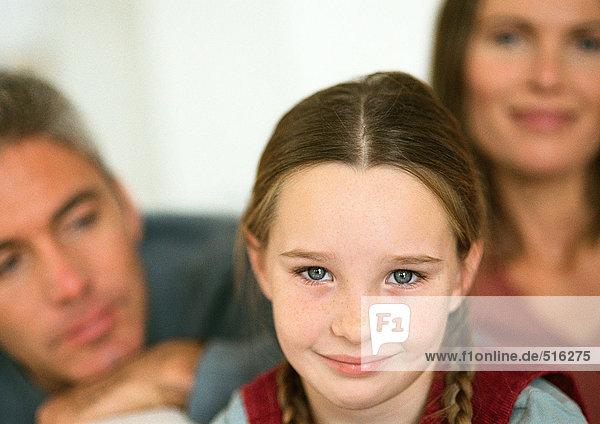 Kleines Mädchen mit lächelnden Zöpfen  erwachsener Mann und Frau im Hintergrund  Nahaufnahme  Porträt