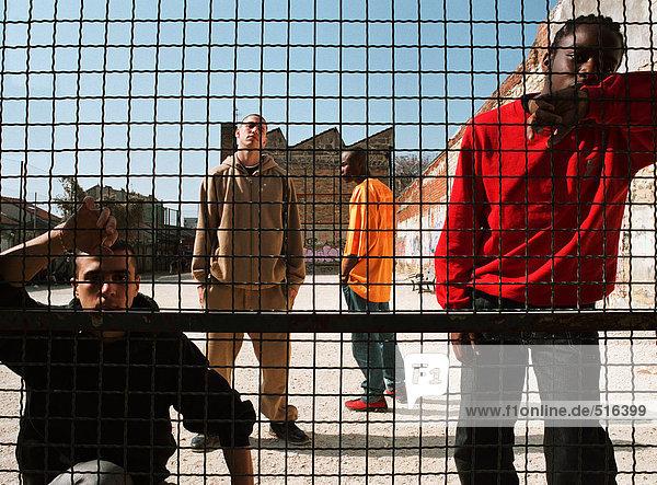 Männer stehen hinter einem Zaun auf einem städtischen Spielplatz.
