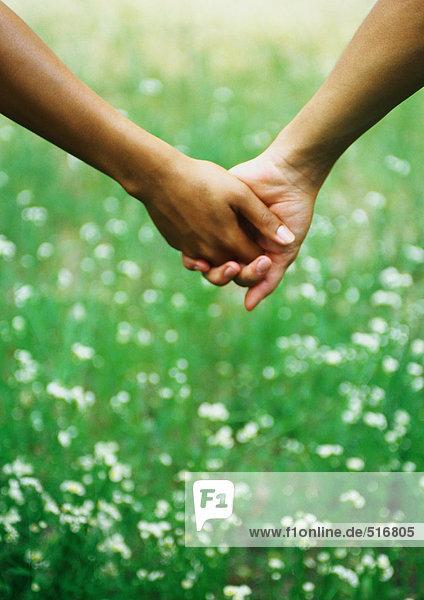 Geklammerte Hände vor Gras mit Wildblumen
