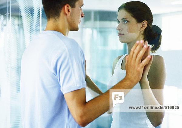 Paar  von Angesicht zu Angesicht  Hände auf beiden Seiten der Glaswand zusammenfügend