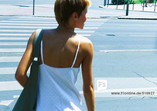 Frau überquert Straße  Rückansicht