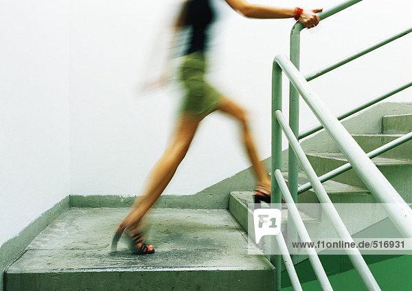 Frau geht die Treppe hinauf  verschwommen