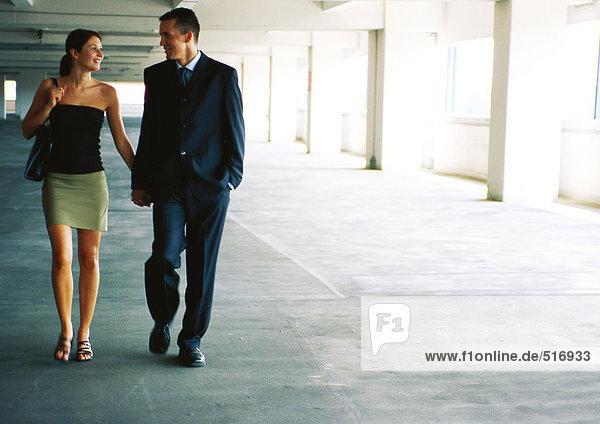 Paar in der Tiefgarage spazieren gehen  lächelnd