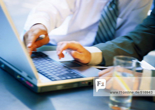 Hände von zwei Geschäftsleuten mit Laptop  Nahaufnahme  unscharf