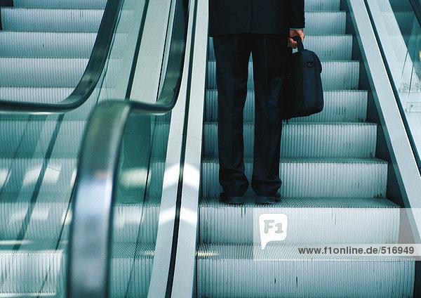 Geschäftsmann auf Rolltreppe  Unterteil