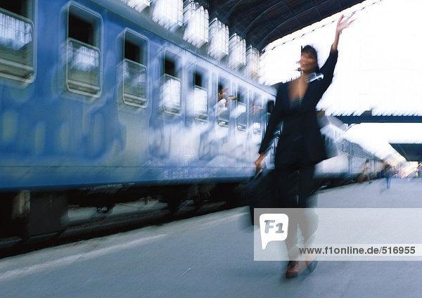 Geschäftsfrau neben dem Zug  winkend  verschwommen