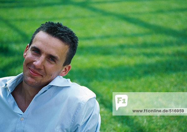 Mann  Kopf geneigt  Kamera lächelnd  grünes Gras im Hintergrund