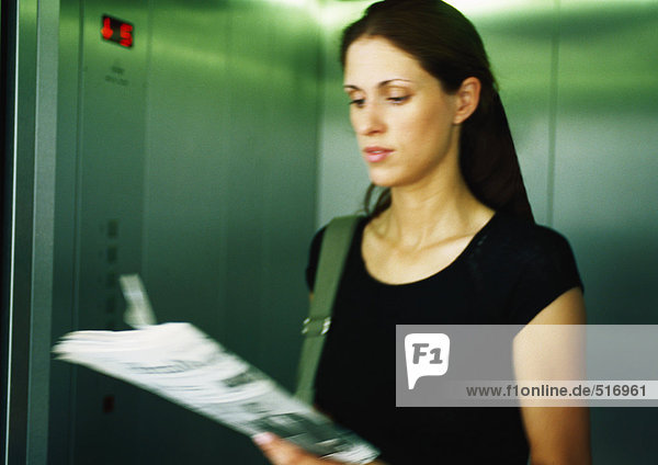Frau liest Zeitung im Aufzug
