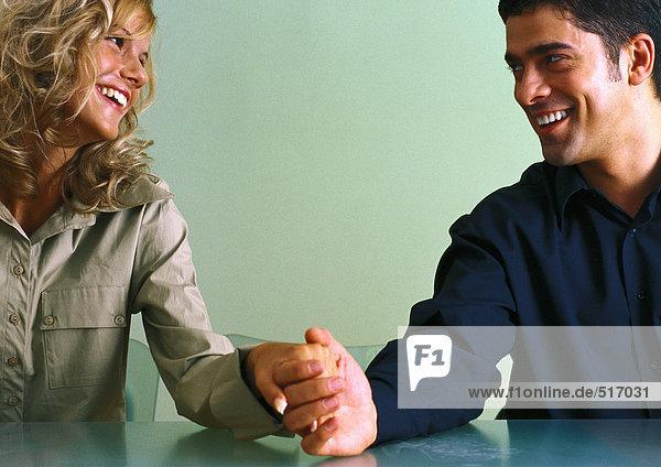 Ein Paar  das am Tisch Händchen hält und sich liebevoll anlächelt.