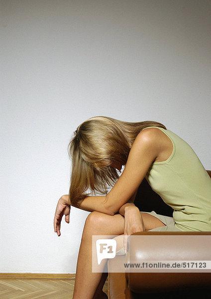 Frau sitzend mit dem Kopf nach unten  Seitenansicht