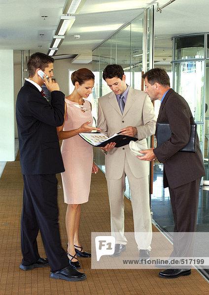Vier Geschäftsleute im Flur stehend
