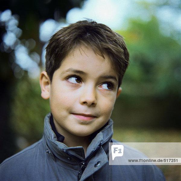 Boy wearing coat outside  looking away  portrait