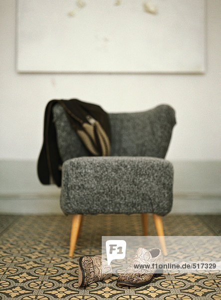 Paar Schuhe vor dem Stuhl mit über dem Rücken drapierter Jacke