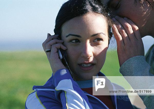 Teenager-Mädchen am Handy  Freund flüstert ihr ins Ohr  Nahaufnahme